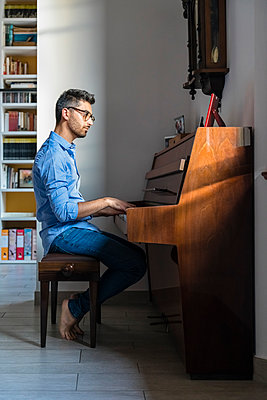 Barefoot young manplaying piano at home - p300m2144087 by Giorgio Magini