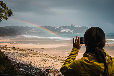 Rear view of woman in raincoat photographing rainbow at beach - p300m2225179 by David Molina Grande