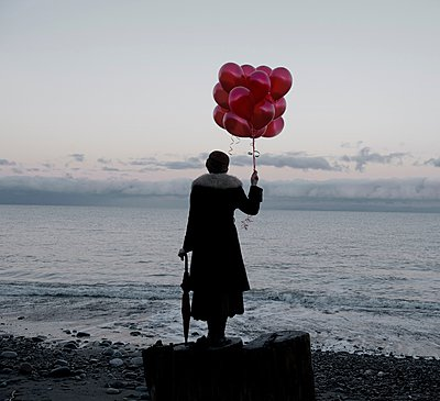 Woman holding bunch of red balloons standing large driftwood tree stump on beach - p924m1054083f by Pete Saloutos