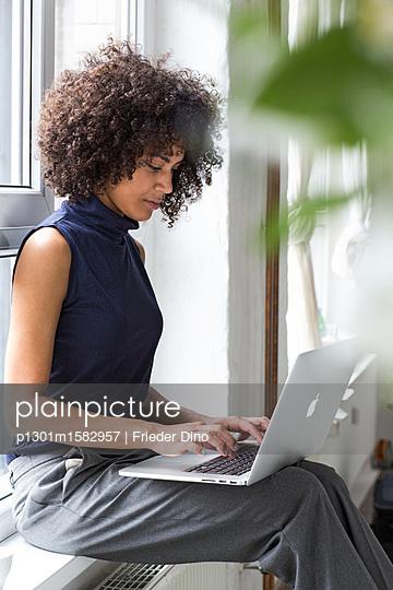 Geschäftsfrau sitzt mit ihrem Laptop auf einer Fensterbank  - p1301m1582957 von Delia Baum