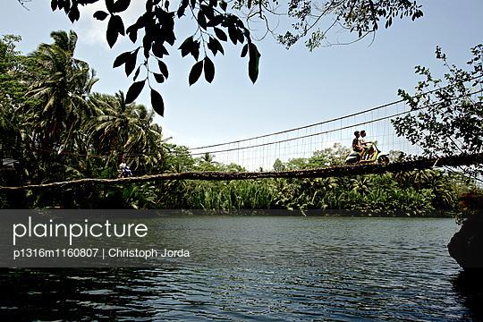 Personen ute fahren mit Motorrollern über eine Hängebrücke, Denpasar, Bali, Indonesien - p1316m1160807 von Christoph Jorda
