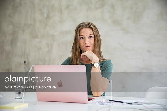 Confident young woman with laptop - p276m2110690 by plainpicture