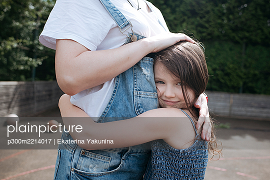 Daughter and mother embracing each other at back yard - p300m2214017 by Ekaterina Yakunina