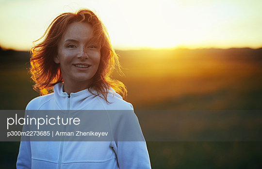 Carefree redhead woman during sunset - p300m2273685 by Arman Zhenikeyev