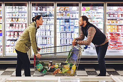 Side view of couple talking while leaning on shopping cart at refrigerated section - p426m1148145 by Maskot