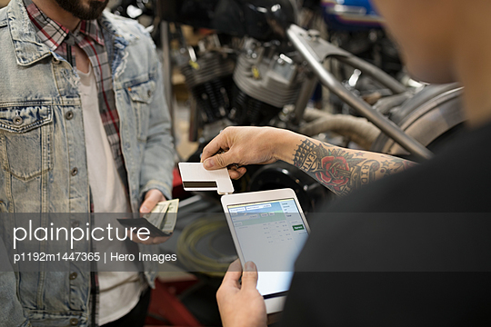 Customer paying motorcycle mechanic with credit card reader and digital tablet in auto repair shop