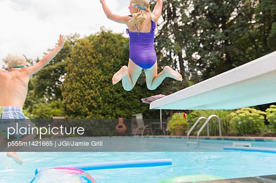 Caucasian children jumping into swimming pool - p555m1421665 by JGI/Jamie Grill