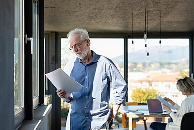 Man reading paper while standing with woman in background at home - p300m2265107 by Emma Innocenti