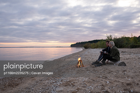 Young couple relaxing with tea near bonfire - p1166m2235275 by Cavan Images