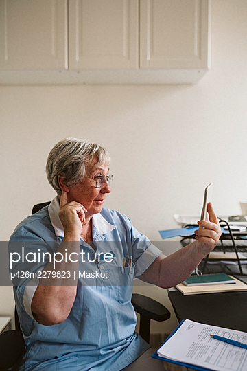 Senior female doctor touching ears while consulting patient through smart phone at medical clinic - p426m2279823 by Maskot