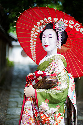 A woman dressed in the traditional geisha style, wearing a kimono and obi, with an elaborate hairstyle and floral hair clips, with white face makeup with bright red lips and dark eyes holding a red paper parasol.  - p1100m1185725 by Mint Images