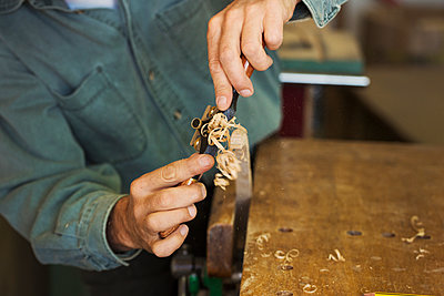 A craftsman using a spokeshave with blade to trim a piece of wood in a clamp.  - p1100m1522488 by Mint Images