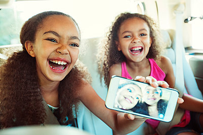 Happy girl showing photograph in smart phone while traveling with sister - p1166m1225969 by Cavan Images