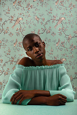 Portrait of a young balck woman with bald head in front of a old tapestry - p1619m2192687 by Laurent MOULAGER