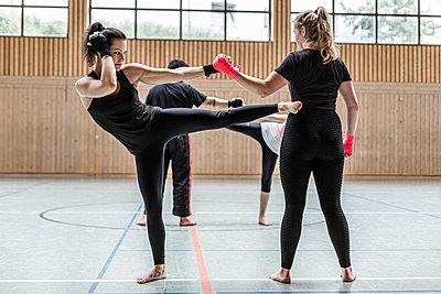 Female kickboxers practising in sports hall - p300m2144854 von Stefanie Baum