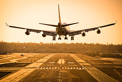A plane landing at sunset.  - p343m1168174 by Rob Hammer