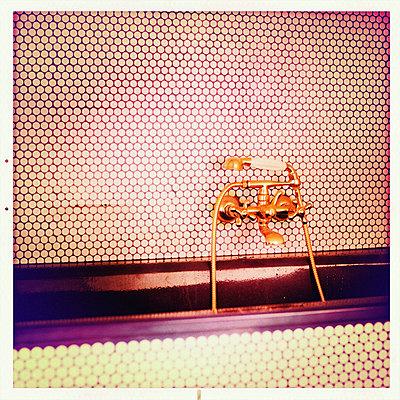 Vergoldete Armatur an einer fein gefliesten Wand - p586m973152 von Kniel Synnatzschke