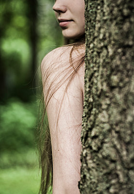 Young woman standing behind tree - p971m1462949 by Reilika Landen