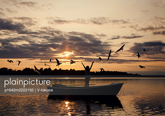 Girl in a boat among seagulls at sunset - p1642m2222192 by V-fokuse