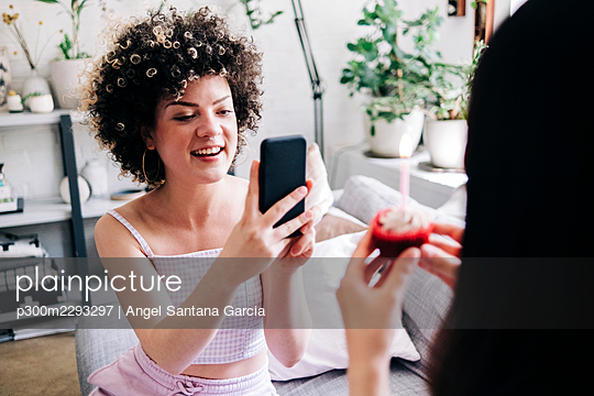 Smiling woman photographing friend through smart phone at home - p300m2293297 by Angel Santana Garcia