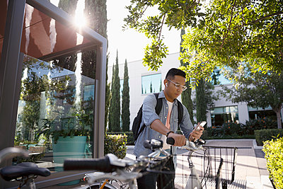 Young man with bicycle using smart phone on sidewalk - p1192m2062461 by Hero Images