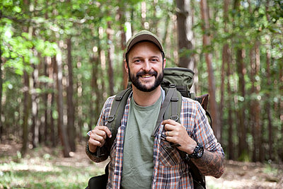 Portrait of smiling man with backpack on a hiking trip in forest - p300m1499384 by Michelle Fraikin