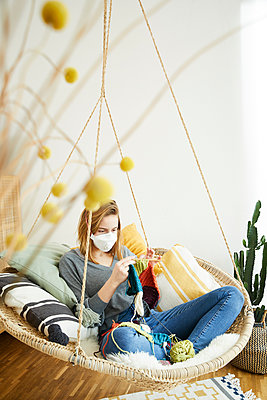 Blond woman wearing FFP2 mask and knitting sitting in hanging chair at home - p300m2188589 by Sandra Bielmeier
