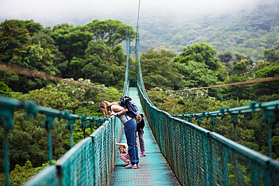Mother with daughters on hanging bridge - p312m1471118 by Anna Kern