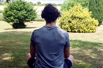 Young man practicing yoga in garden, rear view lotus pose - p429m2032223 by Image Source