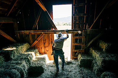 Caucasian farmer resting in barn near bales of hay - p555m1219510 by Inti St Clair