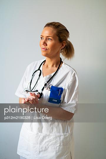 Female doctor looking away - p312m2190328 by Lisa Öberg
