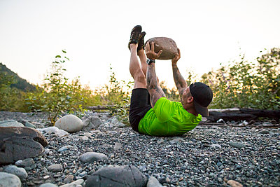 Fit man uses boulder in outdoor fitness routine - p1166m2147263 by Cavan Images