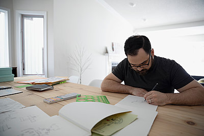 Focused male artist sketching, drawing on paper at table - p1192m1567434 by Hero Images