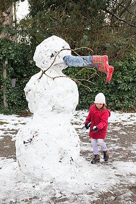 Girl building a snowman - p1231m1225858 by Iris Loonen