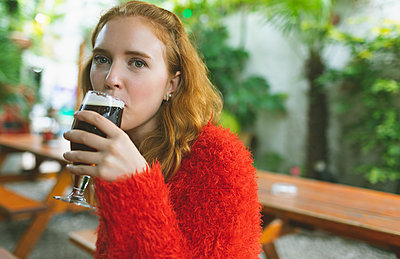 Woman having a glass of beer in outdoor cafe - p1315m2062654 by Wavebreak
