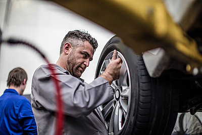 Car mechanic in a workshop changing tire - p300m1189593 by zerocreatives