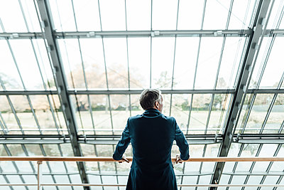 Male entrepreneur looking through window while leaning on railing in office corridor - p300m2266288 by Gustafsson