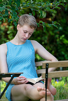 Young woman reading a book in the garden - p427m2134494 by Ralf Mohr
