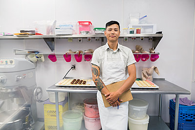 Portrait confident pastry chef with clipboard commercial kitchen - p1192m1063884f by Hero Images