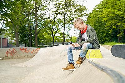 Boy with headphones in skatepark using smartphone - p300m1587012 von Philipp Dimitri