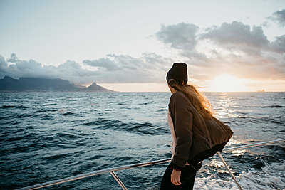 South Africa, young woman with woolly hat during boat trip at sunset - p300m2080842 by letizia haessig photography