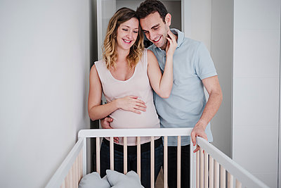 Happy pregnant wife and husband standing by crib at home - p300m2251150 by Eva Blanco