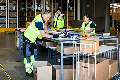 Multi-ethnic workers packing merchandise at distribution warehouse - p426m2018789 by Maskot