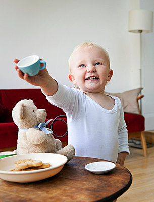 A boy toddler holding out a tea cup - p4297398f by Fiona Jackson-Downes and Dirk Lindner