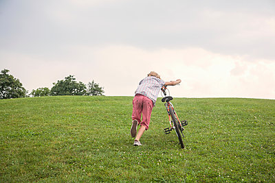 Boy pushing bicycle uphill - p429m2019374 by Seb Oliver
