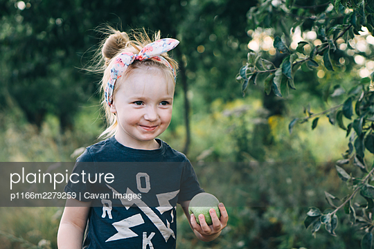 cute girl holds a green apple in her hands - p1166m2279259 by Cavan Images