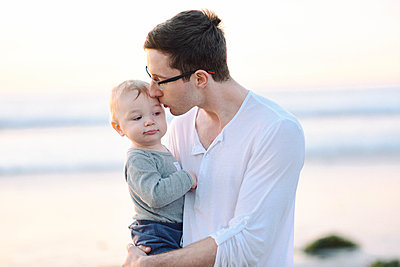 A young father giving his son a kiss on the temple at the beach. - p1166m2162995 by Cavan Images