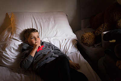 Musing boy on bed, stay at home due to Covid-19 - p1498m2183731 by Nina King