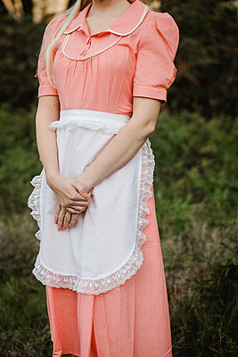 Young woman in pink dress and white apron - p1628m2212010 by Lorraine Fitch