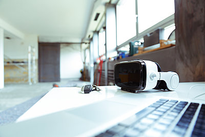 Laptop, keys and Virtual Reality Glasses on table top at construction site - p300m1416746 by realitybites